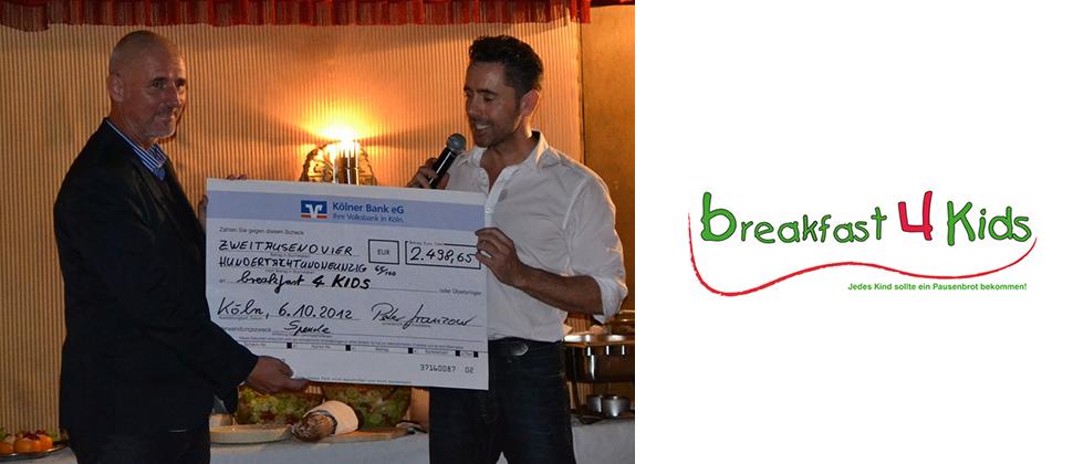 Das Bild zeigt Peter Granzow bei der Übergabe des Spendenschecks in Höhe von 2.498 Euro an den breakfast 4 Kids Vorstand Achim Monnartz